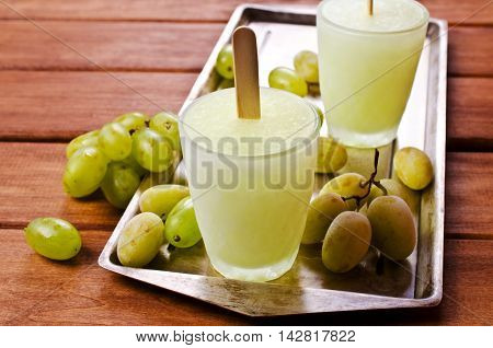 Ice lolly of green grapes on a wooden background. Selective focus.
