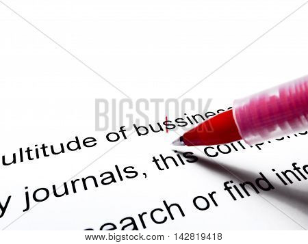Red pen correcting proofread english text isolated on white
