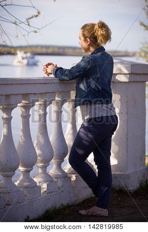 Young blond girl in blue denim jacket standing at the railing and watching the Volga river.