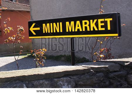 A black and yellow mini market sign