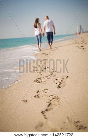 Happy young couple walking on a tropical beach. Lovers in full body length on beach. Back rear view. Honeymoon couple holding hands walking on sand beach. Travel vacation concept.