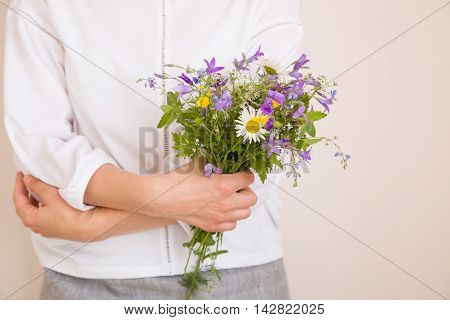 Closeup of woman's hands holding beautiful bunch of wild flowers. Girl with summer bouquet at white wall