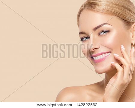 Beauty Woman Portrait. Beautiful Spa Girl Touching her Face and smiling. Perfect Fresh Skin. Pure Beauty Model Female looking at camera. Youth and Skin Care Concept. Beige background