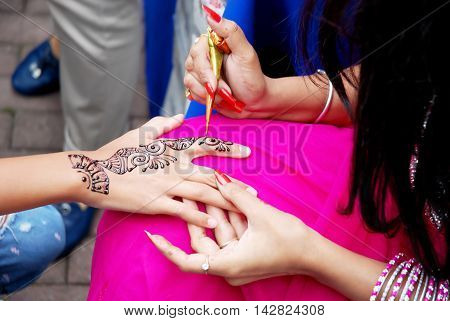 Indian artist paints henna temporary pattern on the girl's hand during the Day of India in Moscow