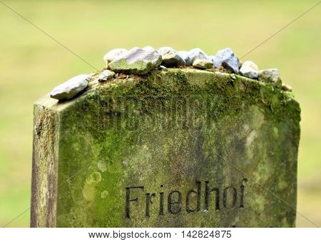 Jewish cemetery with focus on an old tombstone with german