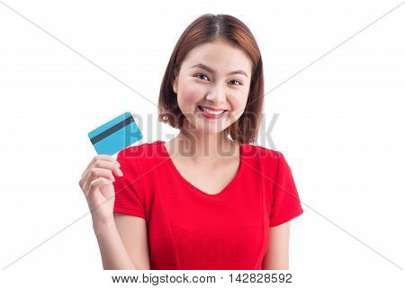 Beautiful friendly smiling asian girl showing credit card in hand over white background