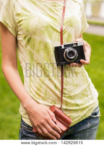 Young beautiful woman with beautiful figure, posing with retro camera making photos, taking pictures. Young photographer and vintage camera outdoors