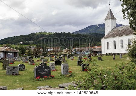 OYSTESSE, NORWAY - JULY 2, 2016: This is Lutheran church with a cemetery in a small village on the shores of Hardangerfjord.