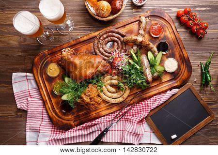 Roast pork and different sausages served with vegetable garnish. Oktoberfest