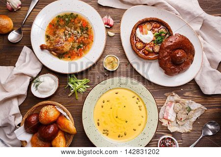Assorted soups on the table, overhead view. Lentil soup with duck. Soup with tomatoes and sausage served in bread bowl. Pumpkin soup.