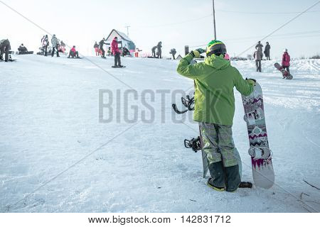 person in ski suit with snowboards looking on the hill view from back