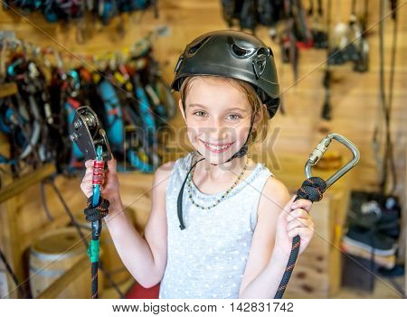 smiling little girl in helmet holding climbing equipment in hands and looking at camera