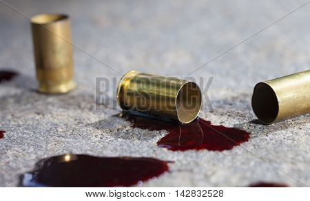 Casings that have been shot from a handgun with blood on concrete