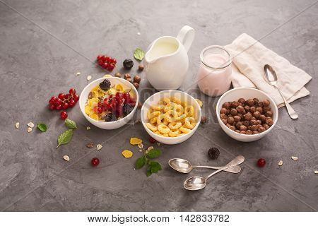 Bowl with corn rings, chocolate balls, homemade granola, berries and milk. Health food concept