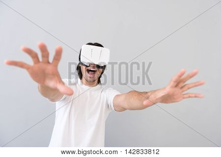 I am coming closer. Cheerful playful young man holding hands in front of him and using virtual reality device