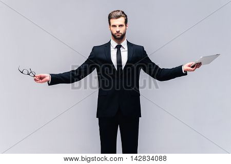 True business. Studio shot of handsome young man in full suit carrying eyeglasses and digital tablet