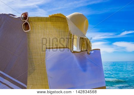 beach with deck chair, towel, bag, hat and sunglasses