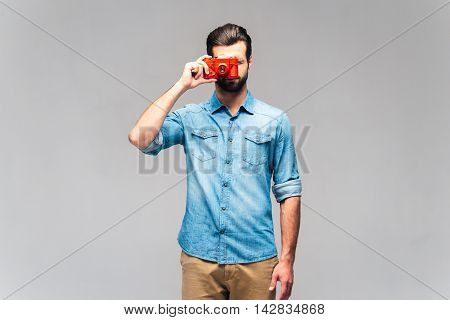 Focusing at you. Studio shot of handsome young man in casual wear holding retro camera near face and focusing at you