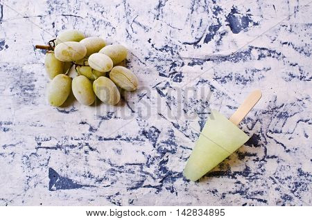 Ice lolly of green grapes on concrete background. Selective focus.