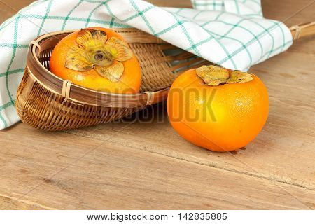 Persimmon yellow color ripe fruits on wood table