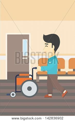 An asian young man pushing empty wheelchair on the background of hospital corridor. Vector flat design illustration. Vertical layout.