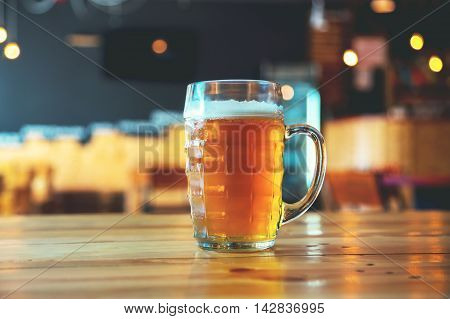 Beautiful Background Of The Oktoberfest. Glass Of Cold Fresh Lager Beer On A Wooden Bar Counter In P