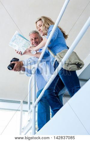 Low angle view of mature couple reading map by railing at home