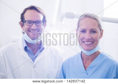 Portrait of dental assistant and dentist wearing surgical mask in dental clinic