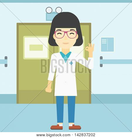 An asian female doctor in medical gown showing ok sign. Smiling doctor gesturing ok sign. Doctor with ok sign gesture in the hospital corridor. Vector flat design illustration. Square layout.
