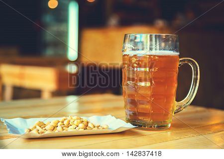 A Fresh Glass Of Cold Light Beer And Salty Peanut On The Wooden Bar Counter In Pub With Free Space F