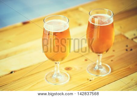 Beautiful Background Of The Oktoberfest. Two Glasses Of Cold Fresh Light Beer On The Wooden Bar Coun