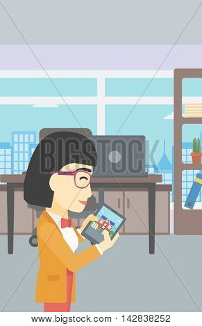 An asian woman looking at house on a digital tablet screen. Young woman standing in office and looking for house on tablet computer. Vector flat design illustration. Vertical layout.