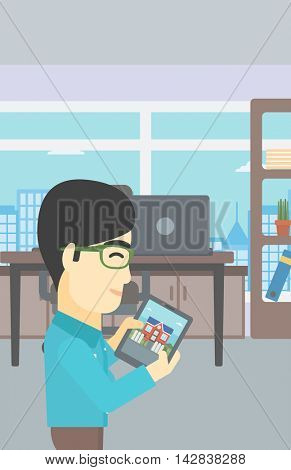 An asian man looking at house on a digital tablet screen. Young man standing in office and looking for house on tablet computer. Vector flat design illustration. Vertical layout.