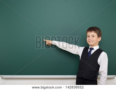 school student boy posing at the clean blackboard, show finger and point at, grimacing and emotions, dressed in a black suit, education concept, studio photo