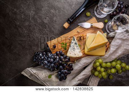 Blue cheese, parmesan, wine and grapes on dark stone background. Food background with copy space