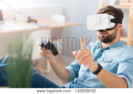 Concentrated on the process. Bearded serious man holding game console and sitting at the table while wearing virtual reality glasses