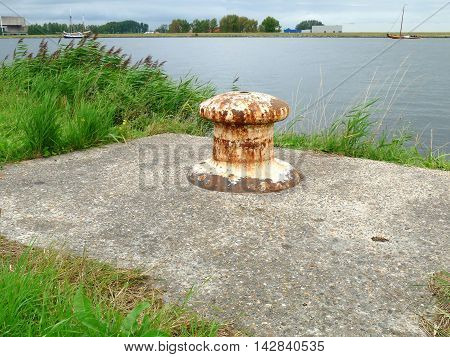 Rusty Bollard On Platform In Grass With Blue River