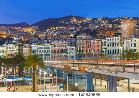 Aerial view of old town, highway and boulevard at night, Genoa, Italy.
