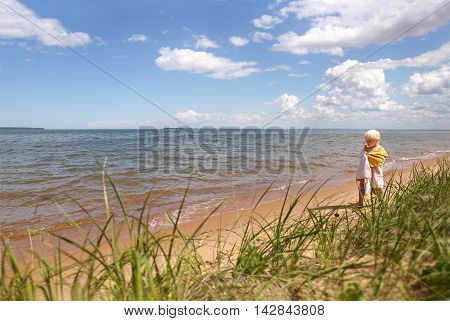 A young boy child in a siwmming suit and beach towel is walking on the sand on the shore of Lake Superior in Wisconsin.