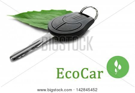 Car key with green leaf trinket and text ecocar on white background. Eco transport concept.
