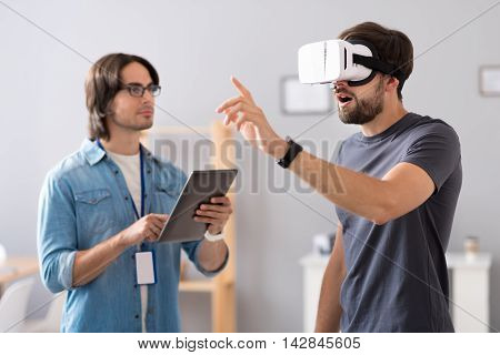 Involved in project. Pleasant concentrated colleagues testing virtual reality glasses while working together in the office