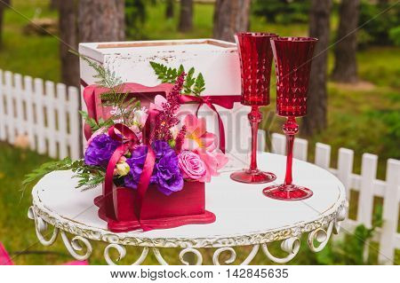 White decorated box, red wineglasses and box with flowers for rings on the table at the wedding ceremony