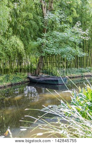 Portrait format image of tranquil water scene with pair of old green wooden boats on a pond surrounded by trees and foliage