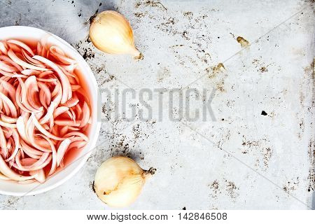 Top view shot of cutted into shreds onion marinated in wine vinegar in white bowl. Traditional home cold appetizer with sour, slightly spicy taste on metal background with fresh onions. Place for text