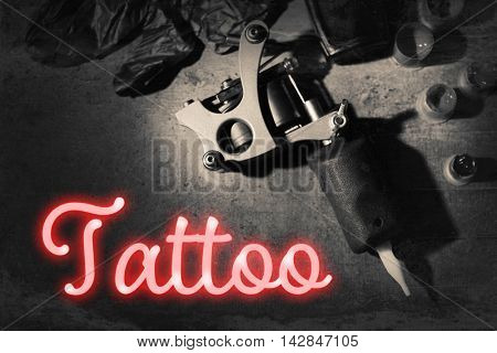 Tattoo machine and tattoo supplies on dark background. Retro style