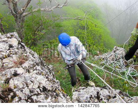Woman climbing on steep the mountain slope. Mountains in Crimea at the sunny summer day.