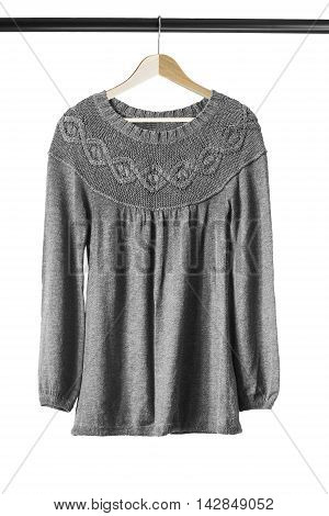 Gray wool sweater on wooden clothes rack isolated over white