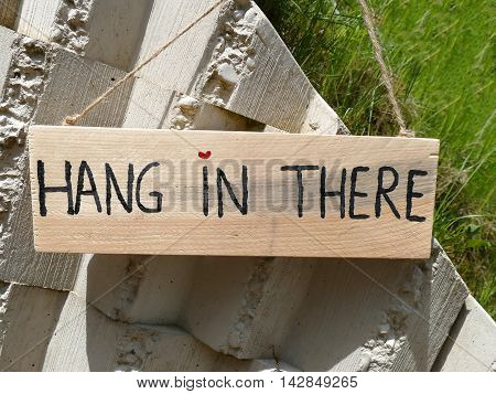 Wooden Sign Hang In There Hanging On Stone Wall With Heart As Dot On I