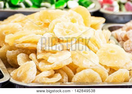 Dried sliced pineapple on the market place. Citrus fruits. Vibrant colors. Healthy food theme.