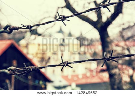 Barbed wire fence in old town Banska Stiavnica Slovak republic. Security theme. Retro photo filter. Travelling in Europe. Private property.